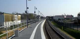 Train tracks to the right with a grey train platform on the left.
