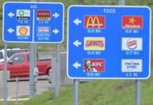 "Specific Service highway signs on the side of highway with grass and a parking lot with trucks behind it. The first sign reads ""Gas"" with four gas station logos and the second sign reads ""Food"" with six food locations."