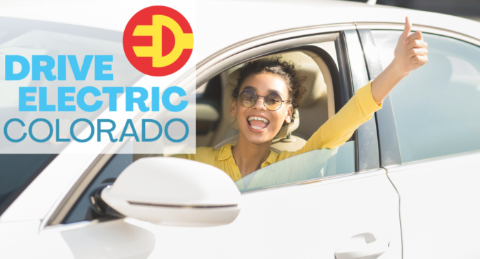A young woman smiles brightly with her arm out of her white car window looking happy. The Drive Electric Colorado logo is in the corner with a red and yellow plug logo.