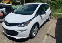 White Chevrolet electric vehicle backed up into a parking spot.