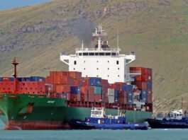 Header photo on shipping container boat on blue waters with land in background