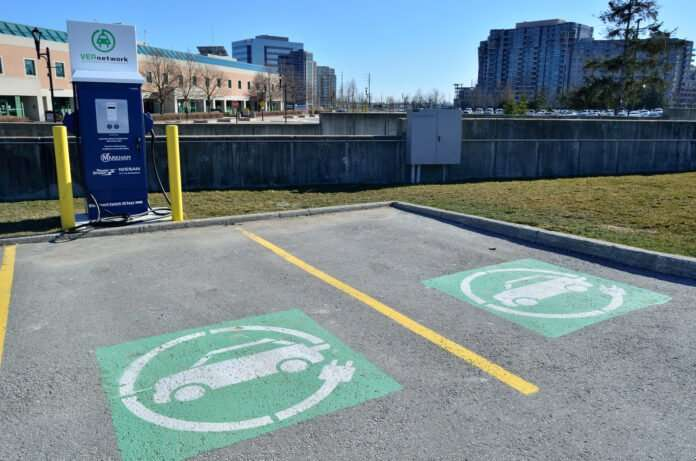 Two empty parking spaces marked with yellow lines featuring green and white electric car logos with a blue electric vehicle charging station stands to the top right