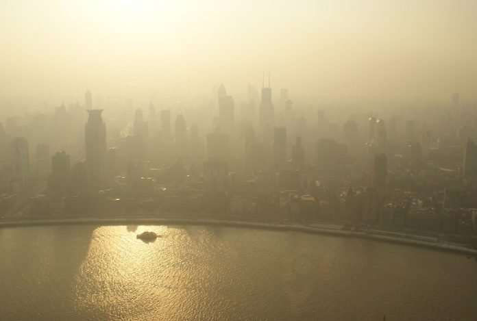 A gray-yellow hazy sky with an city skyline and body of water in front. The entire image shows poor air quality.