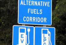 """Blue roadside signage with """"Alternative Fuels Corridor"""" and two fueling images below of an electric vehicle charging unit and a propane autogas refueling station"""