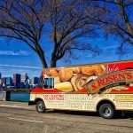 """Large red and tan delivery truck with bread imagery and """"S. Rosen's Baking Company"""" logo sits in front of body of water with Chicago skyline in the background. """"100% Electric Delivery Truck"""" text is on the bottom of the front of the truck."""