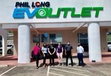 Six people stand in front of the entrance of Phil Long EV Outlet wearing masks. An electric vehicle is parked behind them with a blue balloon.