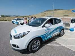 A white and blue hydrogen powered car positioned for display in a parking lot with people in the background.