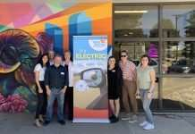 """Seven people stand clustered and smiling around a tall """"Drive Electric Colorado, It's Electric"""" poster in front of a building."""