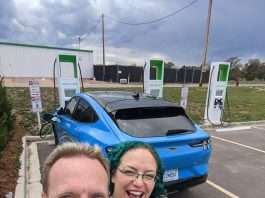 Two people stand taking a selfie in front of their blue Ford Mustang Mach-E electric vehicle. The car is parked in front of three green and white tall DC Fast Charging units.