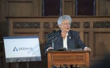 """Alabama Governor Kay Ivey stands behind a brown podium with a microphone speaking. There is a white, """"Alabama Graphite"""" poster board to her right."""