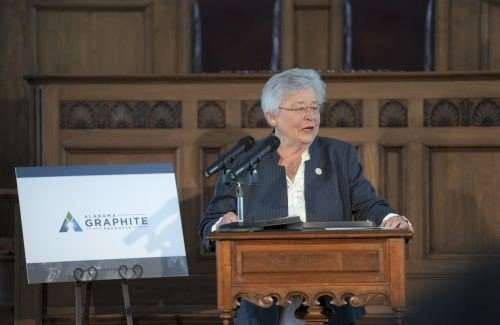 Alabama Governor Kay Ivey stands behind a brown podium with a microphone speaking. There is a white,