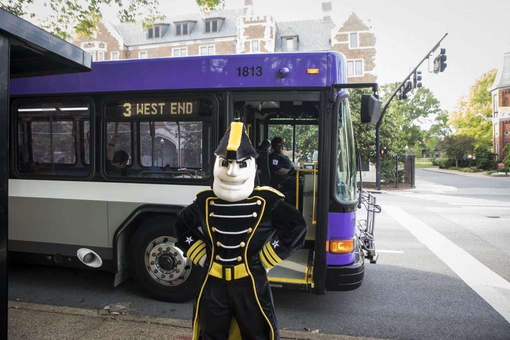 Vanderbilt University mascot posed in front of public transit bus.