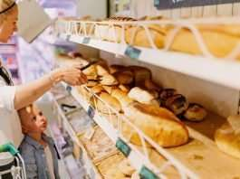 A young woman and small child shop for baked goods. They are standing in front of rows of bread.