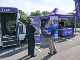 Two men stand with backs to camera, talking. A bus sits to the left with the doors open and an empty driver seat. A purple Endera tent and poster is in the background.