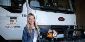 A woman in a white and navy striped dress and jean jacket stands in front of a Moline Public Works truck smiling.